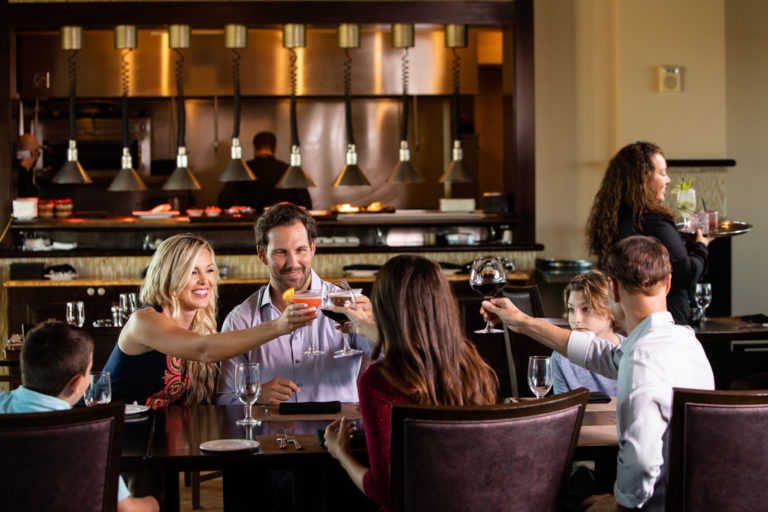 Family raises their drink glasses in a toast at Traditions restaurant.