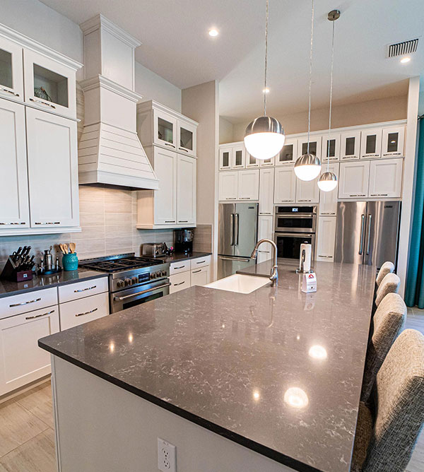 Furnished kitchen with island sink and countertop barstool seating inside a Bear's Den Resort Orlando vacation home.