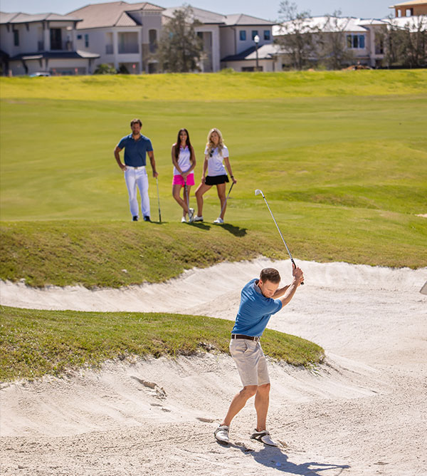Golfer attempts to hit out of a sand trap on the Jack Nicklaus course while 3 friends watch.