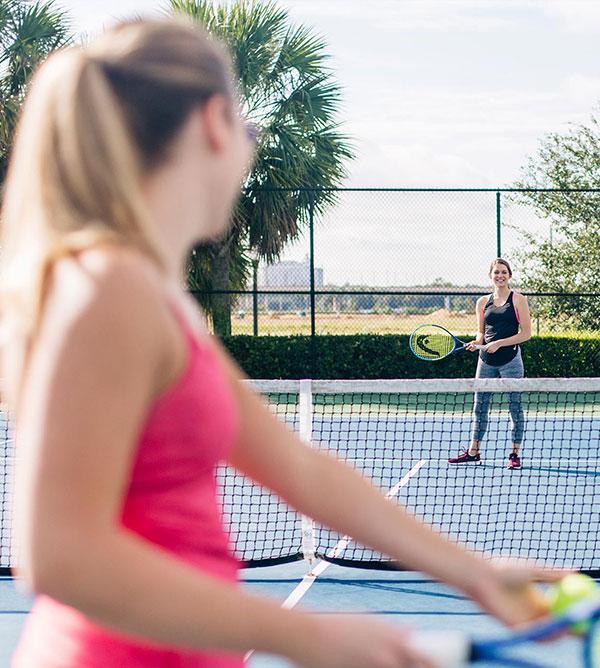 Two women playing tennis at a Reunion resort.