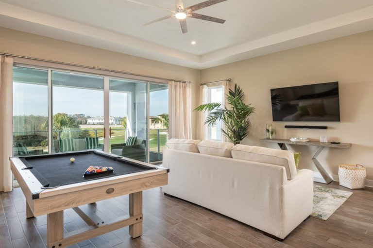 Loft with couch, TV, pool table, and balcony access in an upscale 6-bedroom Bear's Den Resort Orlando residence.