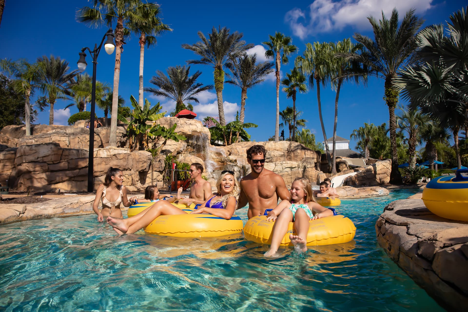 Families riding in tubes on the lazy river ride at the water park at The Bear's Den Resort Orlando.