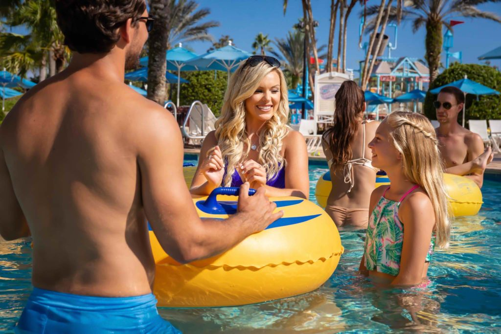 A mom, dad, and daughter standing with a pool float in the Bear's Den Resort Orlando water park.