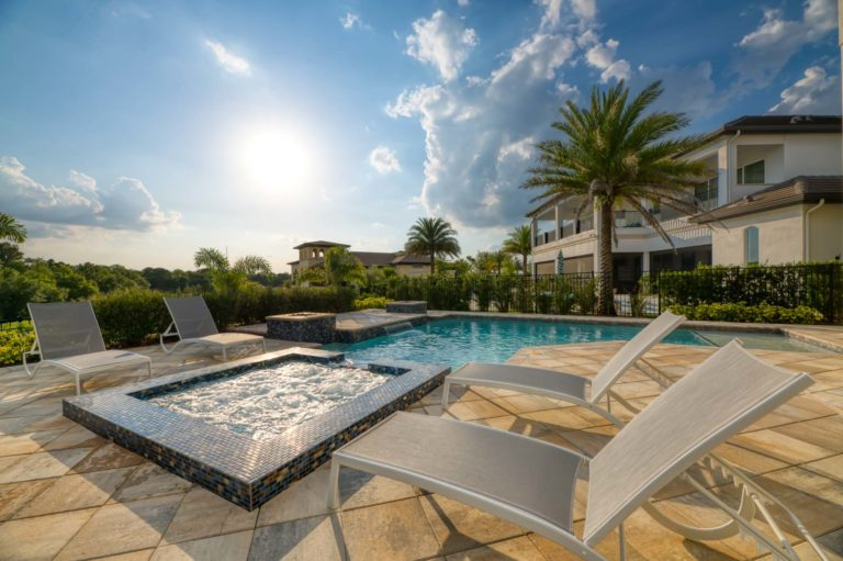 Private backyard patio with pool, hot tub, waterfall, fire pits, and lounge chairs on a sunny afternoon.